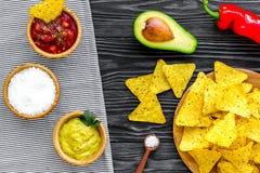 Populära mexikanska mellanmålnachos Den Tiangle nachotortillan nära salsa- och guacamolesause, chilipeppar, saltar på svart trä arkivfoto
