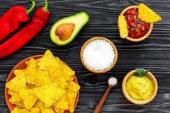 Populära mexikanska mellanmålnachos Den Tiangle nachotortillan nära salsa- och guacamolesause, chilipeppar, saltar på svart trä arkivbild