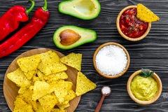 Populära mexikanska mellanmålnachos Den Tiangle nachotortillan nära salsa- och guacamolesause, chilipeppar, saltar på svart trä royaltyfri foto