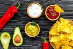 Populära mexikanska mellanmålnachos Den Tiangle nachotortillan nära salsa- och guacamolesause, chilipeppar, saltar på svart trä arkivfoton