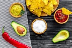 Populära mexikanska mellanmålnachos Den Tiangle nachotortillan nära salsa- och guacamolesause, chilipeppar, saltar på svart trä royaltyfria bilder