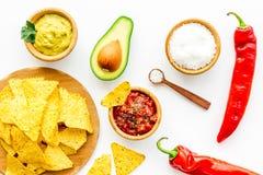 Populära mexikanska mellanmålnachos Den Tiangle nachotortillan nära salsa- och guacamolesause, chilipeppar, saltar på vit royaltyfria foton