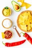 Populära mexikanska mellanmålnachos Den Tiangle nachotortillan nära salsa- och guacamolesause, chilipeppar, saltar på vit royaltyfri foto