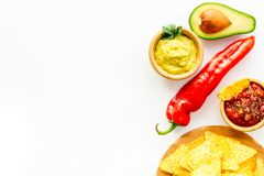 Populära mexikanska mellanmålnachos Den Tiangle nachotortillan nära salsa- och guacamolesause, chilipeppar, saltar på vit royaltyfri fotografi