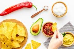Populära mexikanska mellanmålnachos Den Tiangle nachotortillan nära salsa- och guacamolesause, chilipeppar, saltar på vit royaltyfria bilder