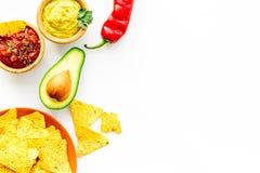 Populära mexikanska mellanmålnachos Den Tiangle nachotortillan nära salsa- och guacamolesause, chilipeppar, saltar på vit arkivfoton