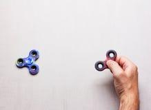 Populäre Spielwaren übergeben Spinner in der männlichen Hand auf grauem Hintergrund mit Raum für Text Stockfotografie