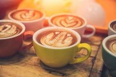 Populäres heißes Getränk der Kaffee Latte-Kunst diente auf hölzerner Tabelle Lizenzfreie Stockfotos