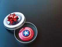 Populaire kleurrijk friemelt spinnerstuk speelgoed in een giftdoos op een zwarte achtergrond Stock Afbeelding