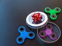 Populaire kleurrijk friemelt spinnerstuk speelgoed in een giftdoos op een zwarte achtergrond Royalty-vrije Stock Afbeeldingen