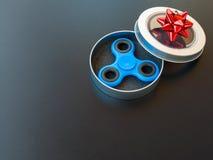 Populaire kleurrijk friemelt spinnerstuk speelgoed in een giftdoos op een zwarte achtergrond Stock Foto