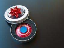 Populaire kleurrijk friemelt spinnerstuk speelgoed in een giftdoos op een zwarte achtergrond Stock Foto's