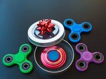 Populaire kleurrijk friemelt spinnerstuk speelgoed in een giftdoos op een zwarte achtergrond Royalty-vrije Stock Afbeelding