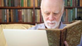 Populaire schrijver die aan laptop thuis op zijn nieuw boek werken Actieve moderne levensstijl van oudere mensen stock video