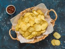 Popular american fast food, beer snack. Corrugated potato chips. In wicker basket on blue grunge background royalty free stock photography