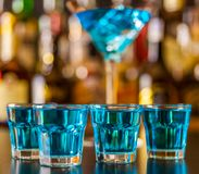 Popular blue drink shot kamikaze on the background of the bar wi. Th bottles, a refreshing drink, party night Royalty Free Stock Images