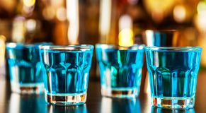 Popular blue drink shot kamikaze on the background of the bar wi. Th bottles, a refreshing drink, party night stock photography