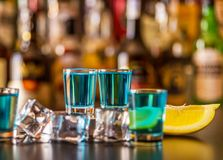 Popular blue drink shot kamikaze on the background of the bar wi. Th bottles, a refreshing drink, party night royalty free stock photos