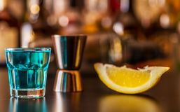 Popular blue drink shot kamikaze on the background of the bar wi. Th bottles, a refreshing drink, party night stock image
