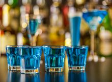Popular blue drink shot kamikaze on the background of the bar wi. Th bottles, a refreshing drink, party night Stock Photos