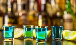 Popular blue drink shot kamikaze on the background of the bar wi. Th bottles, a refreshing drink, party night Royalty Free Stock Image