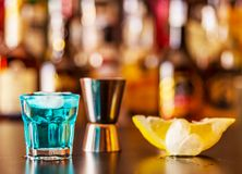 Popular blue drink shot kamikaze on the background of the bar wi. Th bottles, a refreshing drink, party night royalty free stock photo