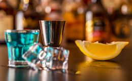Popular blue drink shot kamikaze on the background of the bar wi. Th bottles, a refreshing drink, party night stock photo