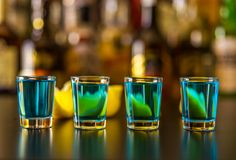Popular blue drink shot kamikaze on the background of the bar wi. Th bottles, a refreshing drink, party night Royalty Free Stock Photography