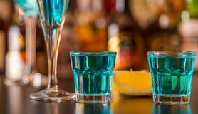 Popular blue drink shot kamikaze on the background of the bar wi. Th bottles, a refreshing drink, party night Stock Images