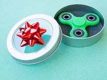 Popular colourful fidget spinner toy in a gift box on a colored background royalty free stock photography