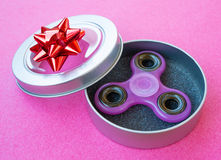 Popular colourful fidget spinner toy in a gift box on a colored background stock photography