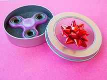 Popular colourful fidget spinner toy in a gift box on a colored background Royalty Free Stock Photo