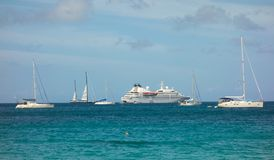 Sailboats and a cruise ship anchored in the shelter of admiralty bay, bequia. A popular destination for yachts and ships as seen from lower bay beach in the Royalty Free Stock Photo