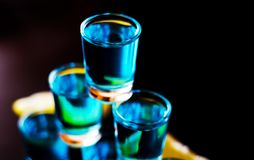 Popular drink shot kamikaze based on vodka, blue curacao and lemon juice, refreshing drink. Party night royalty free stock images