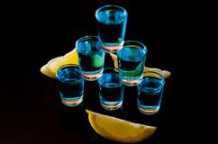 Popular drink shot kamikaze based on vodka, blue curacao and lemon juice, refreshing drink. Party night royalty free stock photography