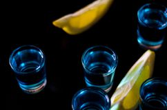 Popular drink shot kamikaze based on vodka, blue curacao and lemon juice, refreshing drink. Party night stock photography