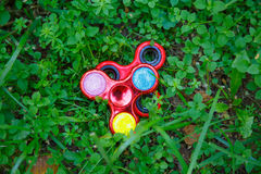 Popular fight spinner toys. In green grass stock photos