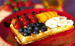The popular foster waffle on a red plate, with fruits. The popular foster waffle on a red plate, with fruit Stock Photo