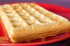 The popular foster waffle on a red plate, with fruits. The popular foster waffle on a red plate, with fruit Royalty Free Stock Images