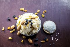 Popular Indian and Asian dessert Suji ka halwa or Rava with organic almonds, cashews and black & golden raisns in a clay bowl on w. Ooden surface royalty free stock images