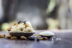 Popular Indian and Asian dessert Suji ka halwa or Rava with organic almonds, cashews and black & golden raisns in a clay bowl on w. Ooden surface royalty free stock photo