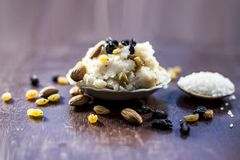 Popular Indian and Asian dessert Suji ka halwa or Rava with organic almonds, cashews and black & golden raisns in a clay bowl on w. Ooden surface royalty free stock image