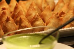 Popular Indian Snack Samosa in a plate. Popular indian snack called Dahi Samosa or samosa dipped in curd, favourite tea time junk food or snack served with Royalty Free Stock Images