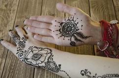 Popular Mehndi Design for Hands painted with Mehandi Indian traditions. Beautiful floral art illustration Mehandi on female hands on wooden background Stock Photography