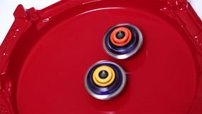 Popular modern children game beyblade burst fast spinning on red arena. Gyroscope, spinner Japanese toy stock video footage