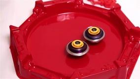 Popular modern children game beyblade burst fast spinning on red arena. Gyroscope, spinner Japanese toy stock footage