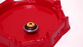 Popular modern children game beyblade burst fast spinning on red arena. Gyroscope, spinner Japanese toy stock video