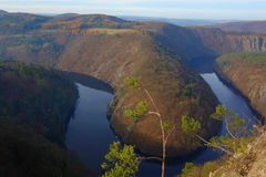 Panoramic view of river canyon with dark water and autumn colorful forest. Horseshoe bend, Vltava river, Czech republic. Beautiful stock image