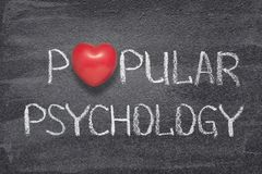 Popular psychology heart. Popular psychology phrase handwritten on chalkboard with red heart symbol instead of O Stock Photo