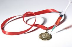Popular red steroid in syringe as a doping stabs a gold medal on a white background. Popular red steroid in syringe as a doping stabs a gold medal with red Royalty Free Stock Photos